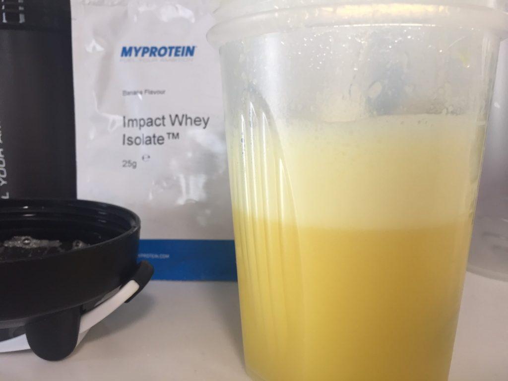 【WPI】Impactホエイアイソレート「Banana Flavour(バナナ味)」を横から写した様子です。泡立ちが確認できます。