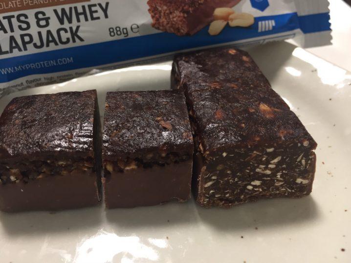 OATS & WHEY FLAPJACK(オーツ & ホエイ)「CHOCOLATE PEANUT FLAVOUR(チョコレートピーナッツ味)」を包丁で切った断面