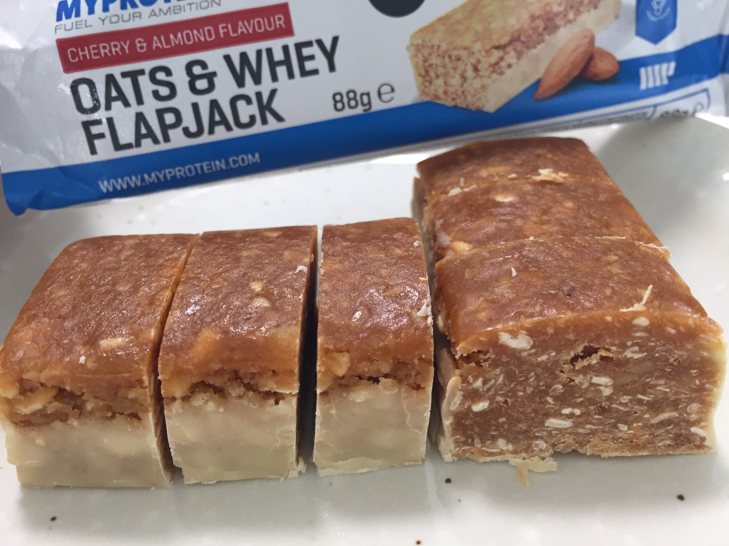 OATS & WHEY FLAPJACK(オーツ & ホエイ)「CHERRY & ALMOND FLAVOUR(チェリー&アーモンド味)」を包丁で切った断面の様子