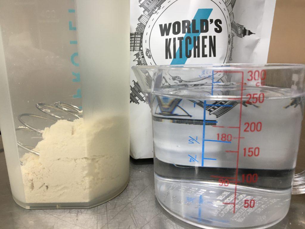 Impactホエイプロテイン:クリームブリュレ味を水に溶かす様子
