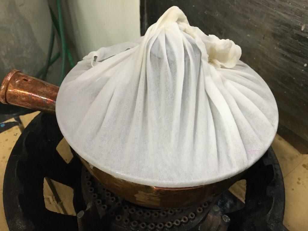 水蒸気が落ちないように濡れ布巾をかけて蓋をする